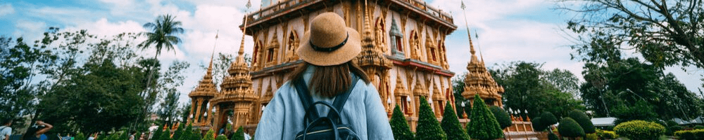 A woman wearing a hat facing a Buddhist temple in Thailand