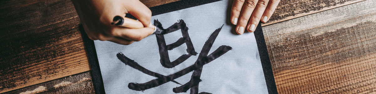 A person writing in Japanese with a paint brush