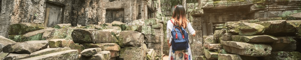 A woman walking through ruins in Cambodia