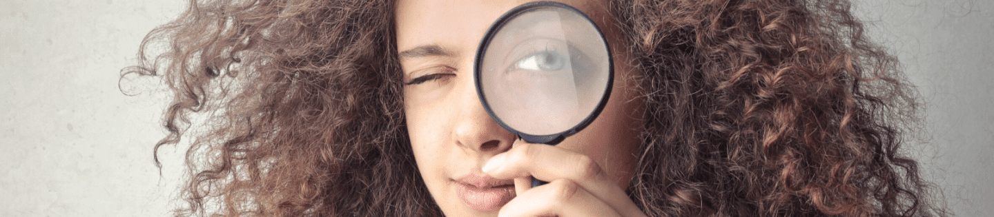 A woman holding up a magnifying glass to her eye