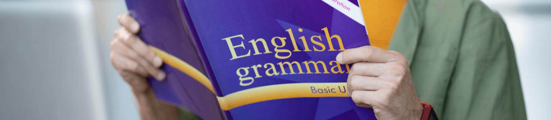 A man holding an English grammar book