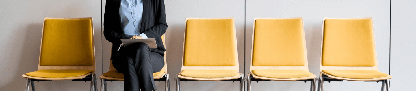 A woman waiting on a yellow chair for an interview