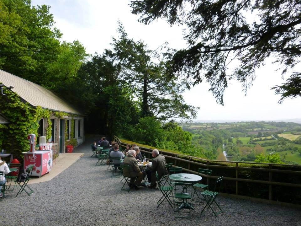 People sitting at tables in front of a French landscape