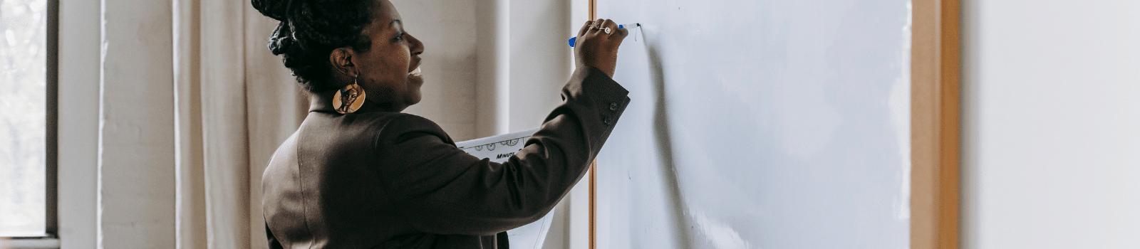 A woman writing on a whiteboard