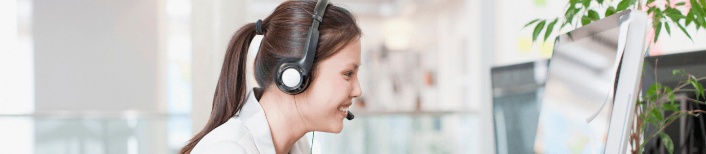 A woman wearing a headset sitting at her computer