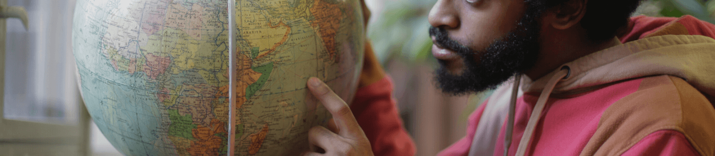 A man looking at a globe and pointing at a country