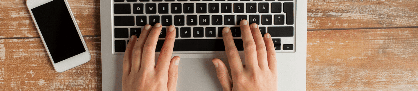 A person typing on a laptop with their phone to the left