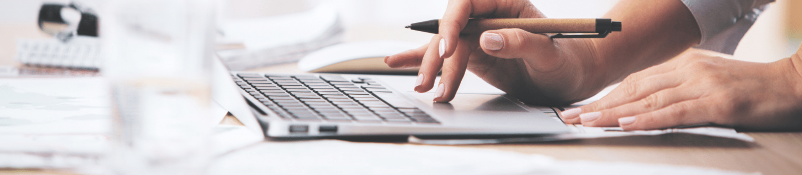 A woman holding a pen and typing on a laptop