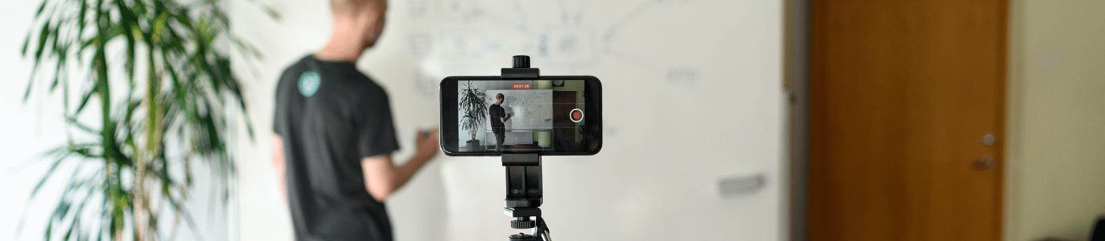 Male teacher recording a lesson via a phone