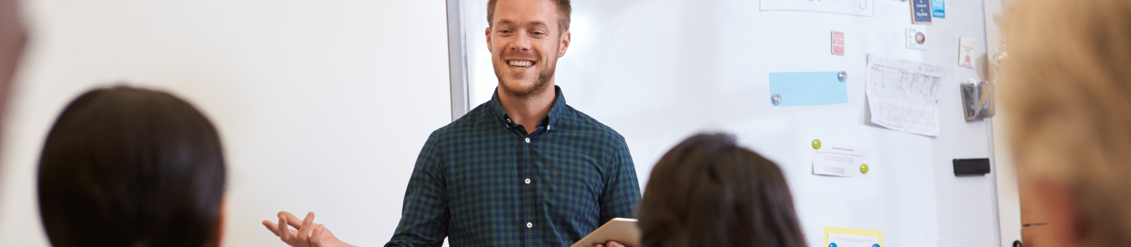 A male teacher standing in front of a whiteboard
